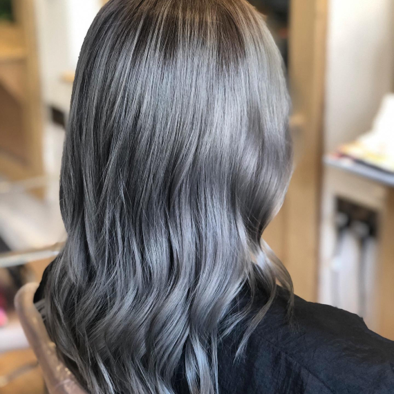 back of woman's head with mid-length hair in metallic ash gray