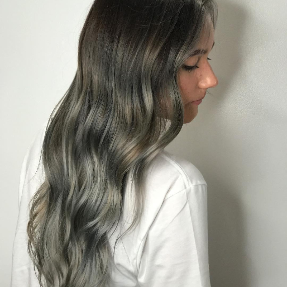 woman with long, wavy hair in ash gray balayage