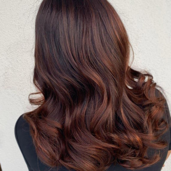 Back of woman's head with loosely curled, dark auburn hair, created using Wella Profes-sionals.