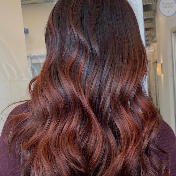 Back of woman's head with tousled, auburn red hair, created using Wella Professionals.