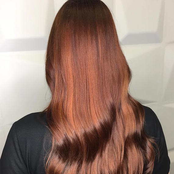 Back of woman's head with long, wavy, auburn hair and highlights, created using Wella Pro-fessionals.