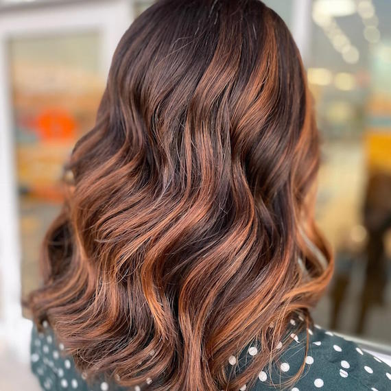 Back of woman's head with wavy, brown hair and auburn highlights, created using Wella Professionals.