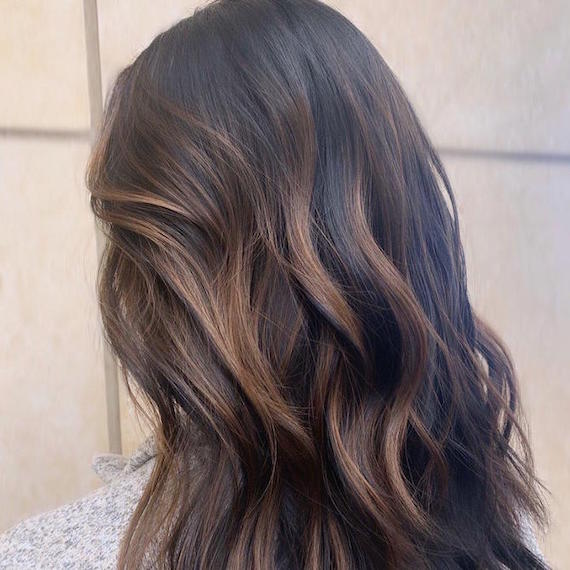 Back of woman's head with long, wavy, dark brown hair and partial balayage, created using Wella Professionals.