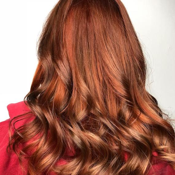 Back of woman's head with long, wavy, pumpkin spice hair, created using Wella Professionals.