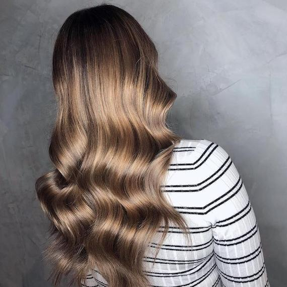 Back of woman's head with long, wavy hair and dark ash blonde balayage, created using Wella Professionals.