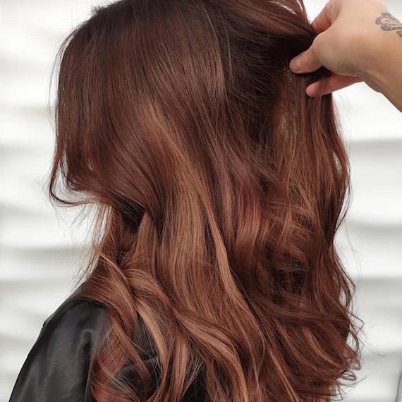 Side profile of woman with wavy auburn hair, created using Wella Professionals.