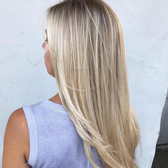 Back of woman's head with long, straight, blonde hair and babylights, created using Wella Professionals.