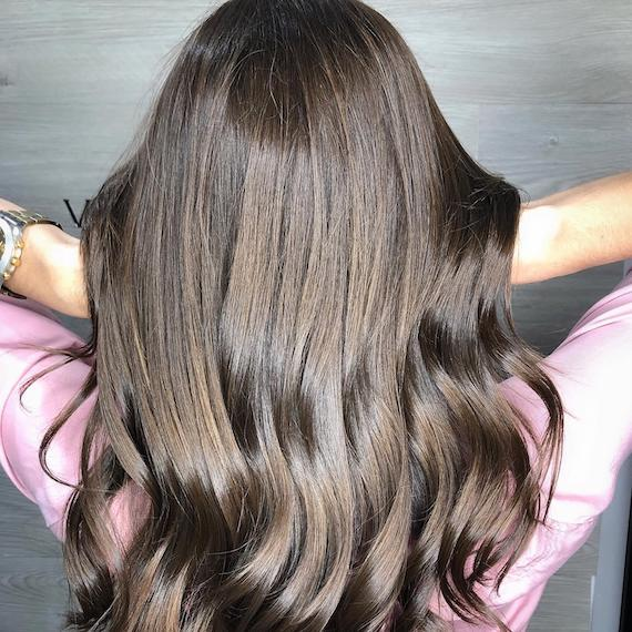 Back of woman's head with long, dark brown hair and babylights, created using Wella Professionals.