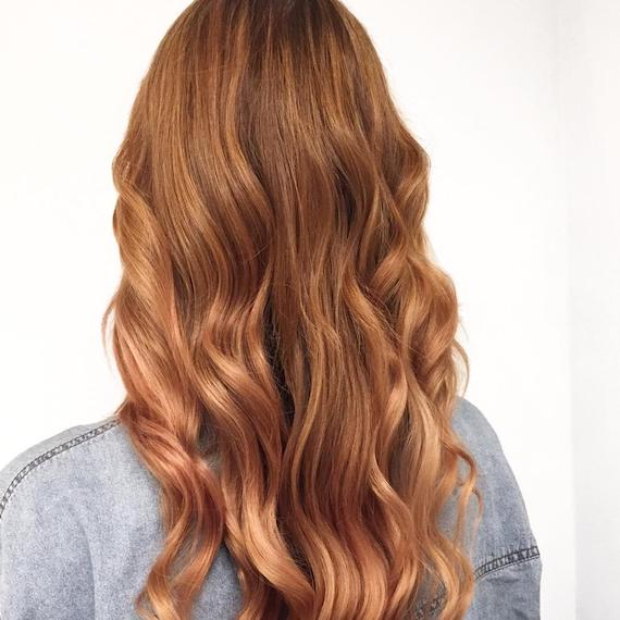 Back of a woman's head with long, wavy strawberry blonde hair and babylights, created using Wella Professionals.