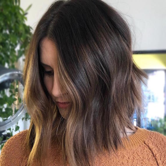 Photo of woman with a brunette balayage bob styled in a very loose, tousled wave, created using Wella Profession-als.