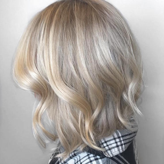 Side profile of woman with ash blonde balayage bob styled in loose waves, created using Wella Professionals.
