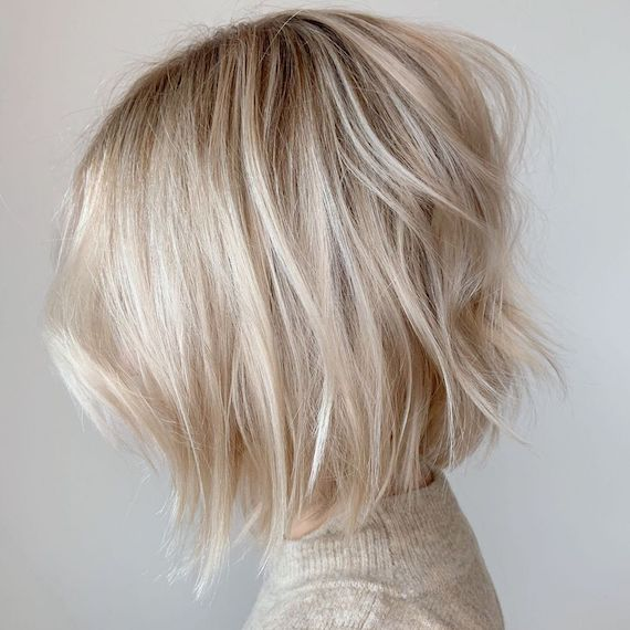 Side profile of woman with light blonde balayage bob, created using Wella Professionals.