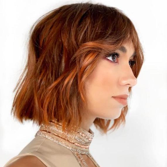 Photo of woman with wavy copper balayage bob, created using Wella Professionals.
