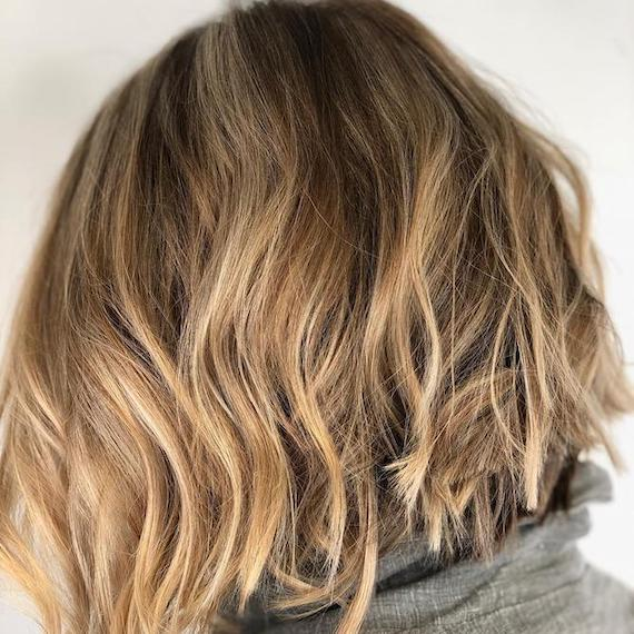 Back of woman's head with beachy blonde balayage through a bob, created using Wella Professionals.