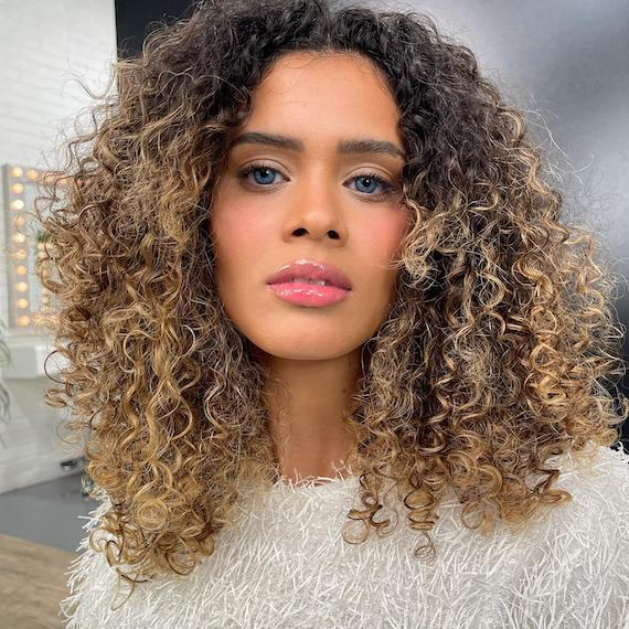 Woman faces camera with shoulder-length curls and blonde balayage, created using Wella Professionals.