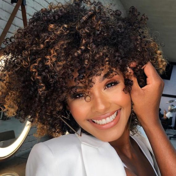 Woman smiles at the camera with curly, dark brown hair and chocolate balayage, created using Wella Professionals.
