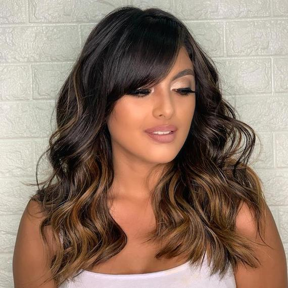 Photo of woman with brunette balayage and bangs, created using Wella Professionals.