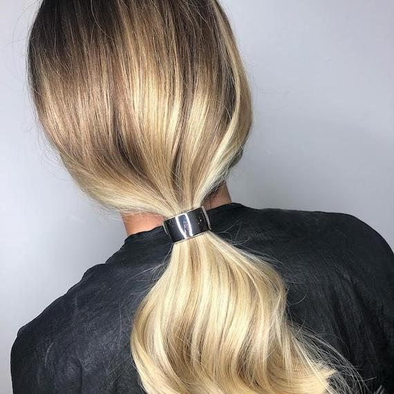 Back of woman's head with blonde, balayage ponytail, created using Wella Professionals.