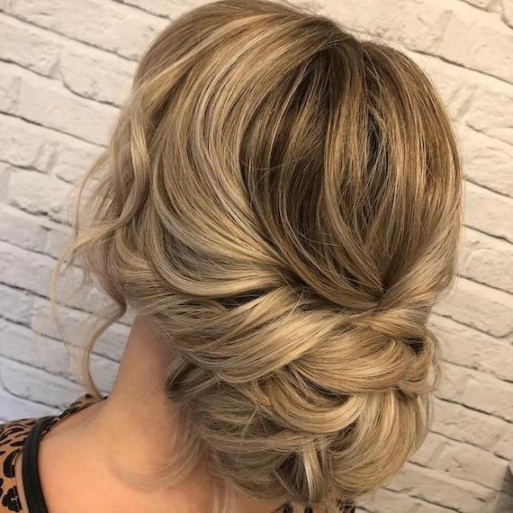 Back of woman's head with blonde, balayaged chignon, created using Wella Professionals.