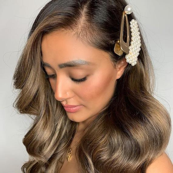 Photo of woman with brunette balayage and a hair accessory, created using Wella Professionals.