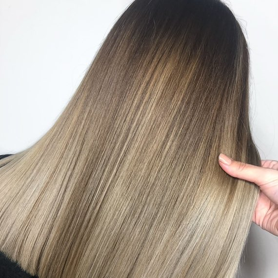 Back of woman's head with ash bronde balayage through straight hair, created using Wella Professionals.