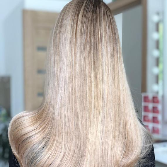 Back of woman's head with vanilla blonde balayage through straight hair, created using Wella Professionals.