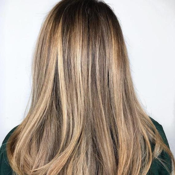 Back of woman's head with dirty blonde balayage through straight hair, created using Wella Professionals.