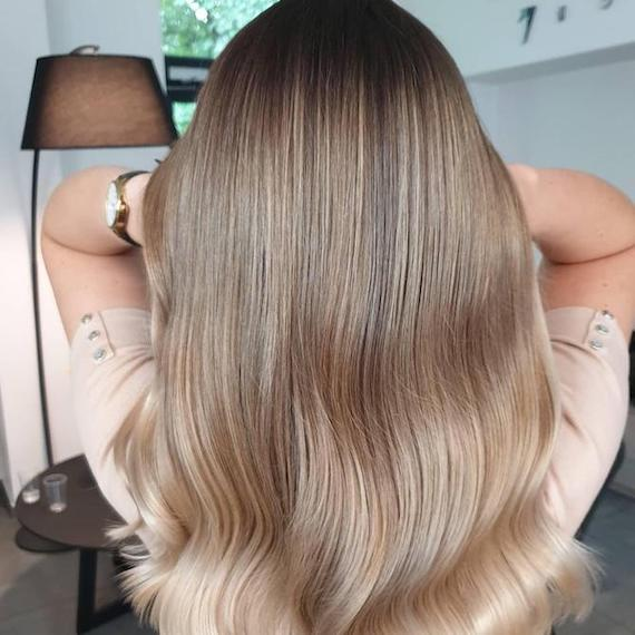 Back of woman's head with cool blonde balayage through straight hair, created using Wella Professionals.