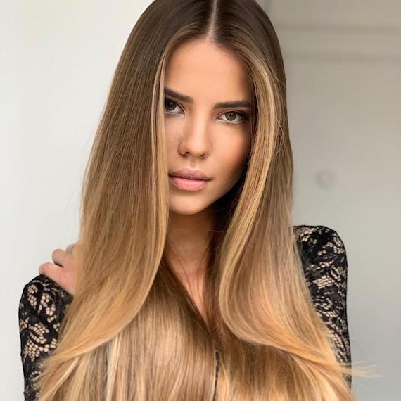 Photo of woman with caramel blonde balayage through straight hair, created using Wella Professionals.