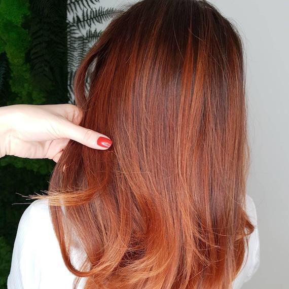 Back of woman's head with auburn balayage through straight hair, created using Wella Professionals.