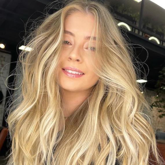 Woman facing camera with voluminous, beach blonde, wavy hair, created using Wella Professionals.
