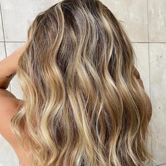 Back of woman's head with beachy, caramel blonde wavy hair, created using Wella Professionals.