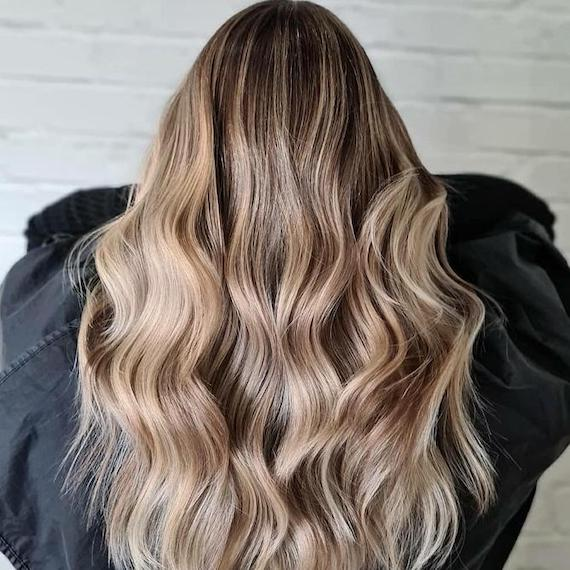 Back of woman's head with long, cool, beach blonde hair, created using Wella Professionals.