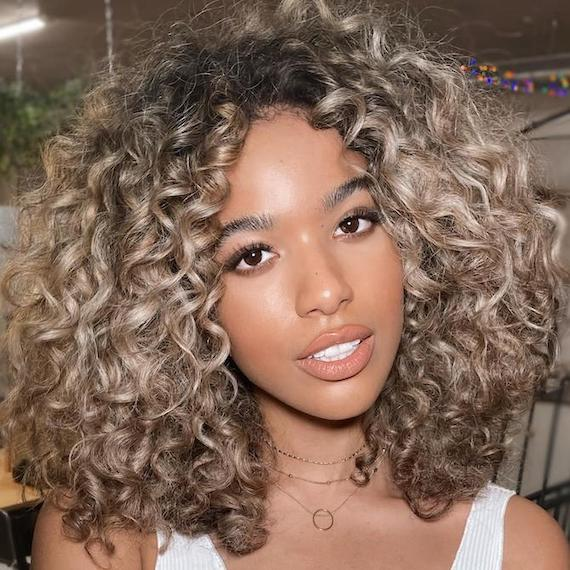 Woman facing camera with curly, beachy, beige blonde hair, created using Wella Professionals.