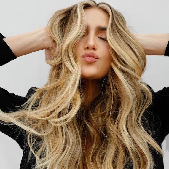 Woman facing camera with long, wavy, beachy hair, created using Wella Professionals.