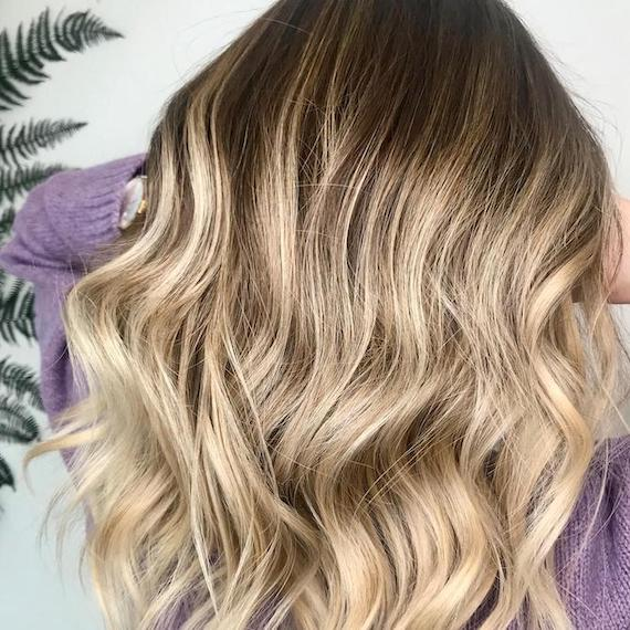Back of woman's head with cool-toned, wavy hair, created using Wella Professionals.