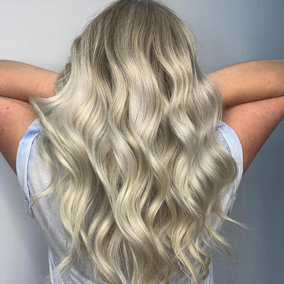 Back of woman's head with long, wavy, beige blonde hair, created using Wella Professionals.
