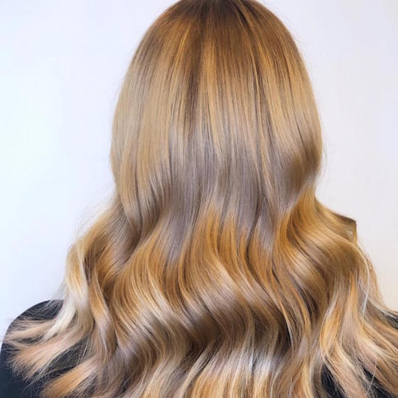 Back of woman's head with medium beige blonde hair, created using Wella Professionals.