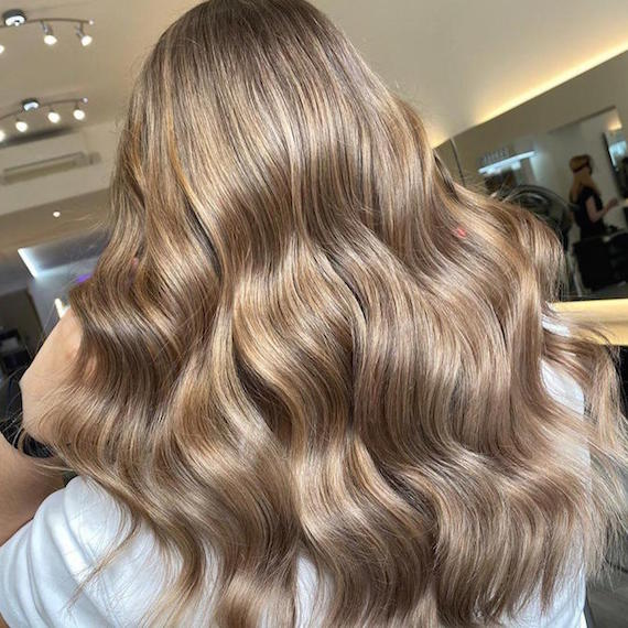 Back of woman's head with dark beige blonde hair, created using Wella Professionals.
