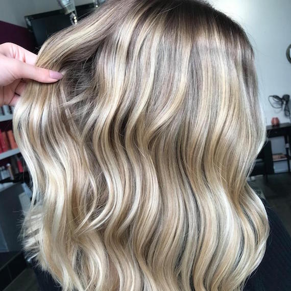 Side profile of woman with wavy, beige blonde hair, created using Wella Professionals.