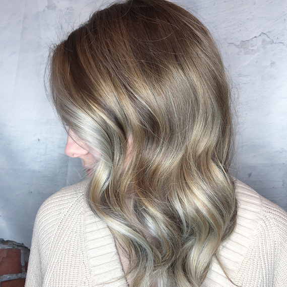 Side profile of woman with long, wavy hair and ash blonde balayage, created using Wella Professionals.