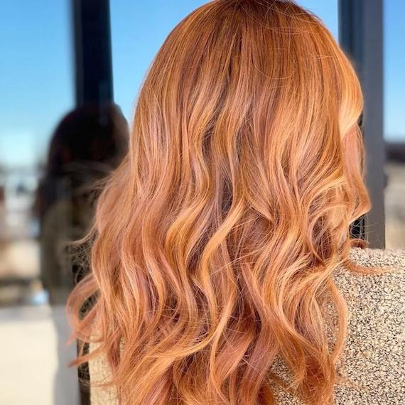 Back of woman's head with long, wavy, strawberry blonde balayage, created using Wella Professionals.