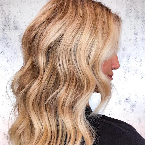 Side profile of woman with long, wavy hair and honey blonde balayage, created using Wella Professionals.
