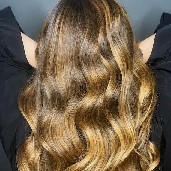 Back of woman's head with long, loosely-curled hair and dirty blonde balayage, created using Wella Professionals.
