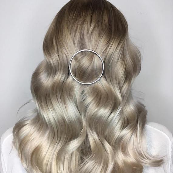 Back of woman's head with long, loosely-curled hair and icy blonde balayage, created using Wella Professionals.