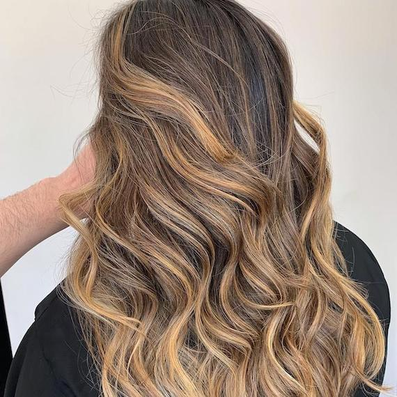 Back of woman's head with light brown balayage through wavy hair, created using Wella Professionals.