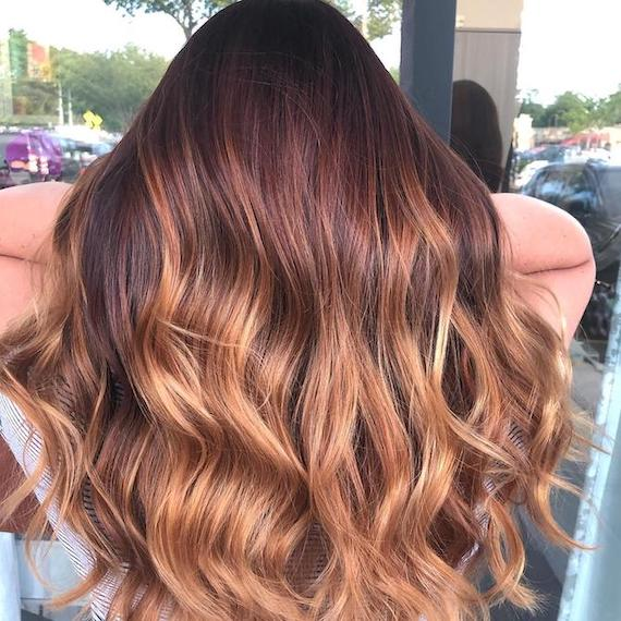 Back of woman's head with red brown to strawberry blonde balayage, created using Wella Professionals.
