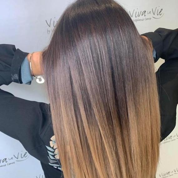 Back of woman's head with straight hair and a brown to blonde dip-dye, created using Wella Professionals.