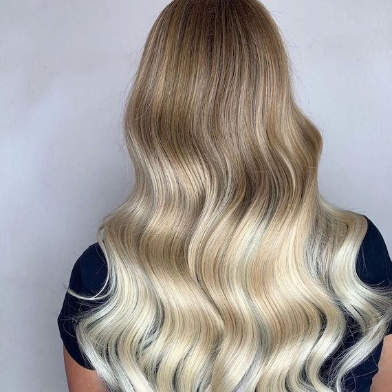 Back of woman's head with wavy hair and a dark blonde to light blonde dip-dye, created using Wella Professionals.
