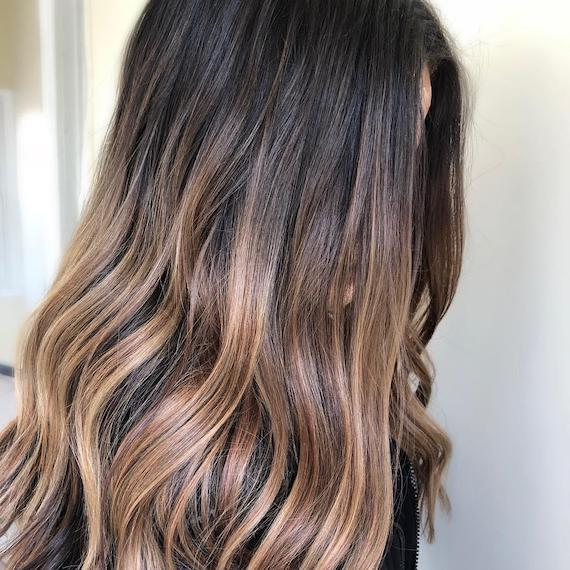 Side profile of woman with long, wavy brown hair and a toffee blonde dip-dye, created using Wella Professionals.